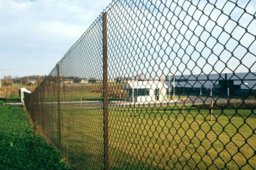 Long chain link fencing protecting a lawn area in Singapore