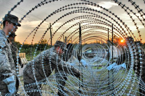 Dedicated workers installing concertina-wire for enhanced security provided by a reliable fencing supplier