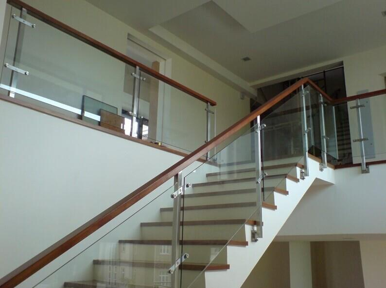 Unique glass railing with timber handrail of an interior staircase designed by Brooklynz Singapore