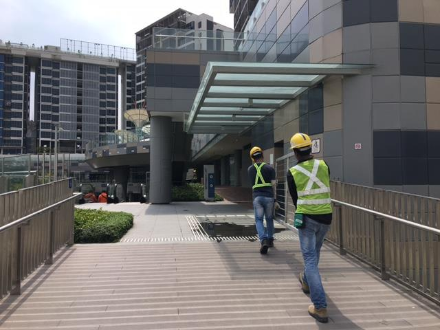 Two workers carrying affordable mild steel gate into a building in Singapore
