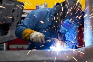 Man doing welding of stainless steel structure with a protective shield